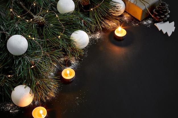 Kerst xmas speelgoed brandende kaarsen en vuren tak op zwarte achtergrond bovenaanzicht ruimte voor tekst