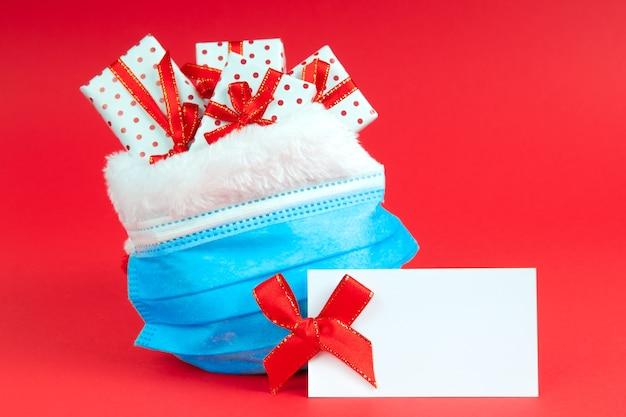 Kerst zak kerstman met geschenken in beschermend gezichtsmasker met mock up. vakantie tijdens virus.