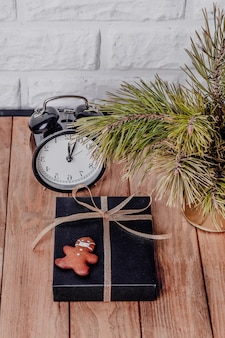 Kerst zakelijke samenstelling. geschenken, zwarte en gouden versieringen op houten achtergrond. koekjes in de vorm van een man met een masker. vakantieconcept in het kader van de coronaviruspandemie