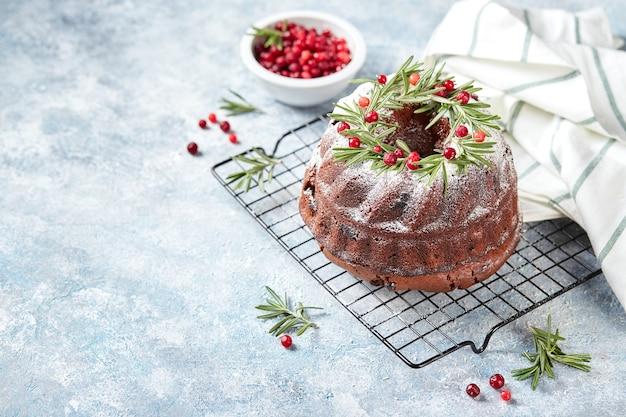 Kerst zelfgebakken donkere chocolade bundt cake versierd met poedersuiker en verse veenbessen op metalen rooster op lichtblauwe achtergrond
