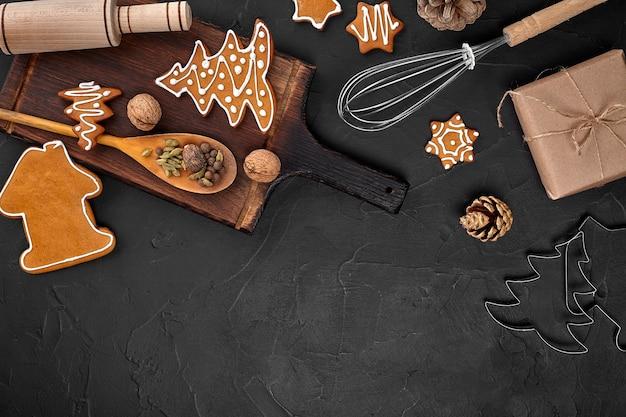 Kerst zelfgemaakte peperkoek koekjes kruiden en snijplank op donkere achtergrond met kopie ruimte voor...