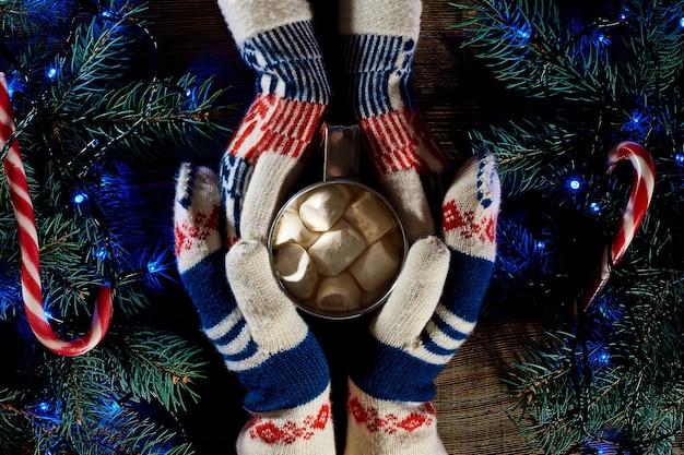 Kerst zelfgemaakte warme chocolademelk met marshmallows in de handen van man en vrouw bovenaanzicht