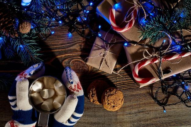 Kerst zelfgemaakte warme chocolademelk met marshmallows in de handen van vrouw bovenaanzicht