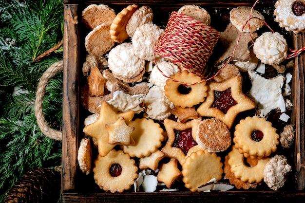 Kerst zelfgemaakte zandkoekjes koekjes collectie verschillende vormen, inclusief traditionele linz koekjes met rode jam in houten bakje over thuja takken als oppervlak. plat leggen, ruimte