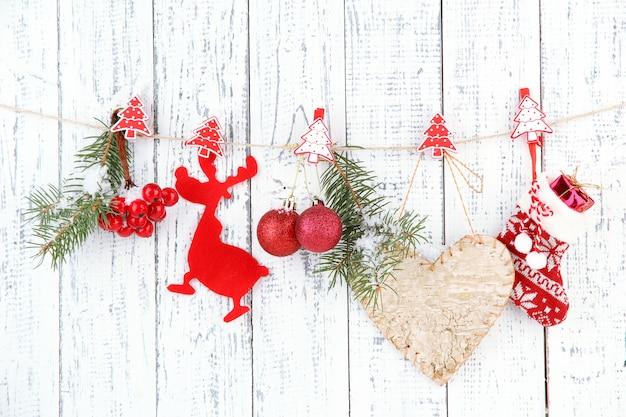Kerstaccessoires die aan een witte houten muur hangen