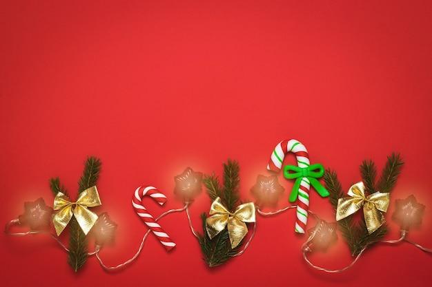 Kerstaccessoires met slinger op een felrode achtergrond.