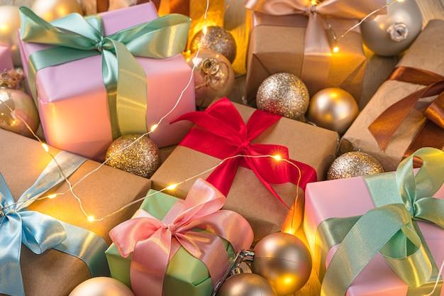 Kerstachtergrond met cadeautjes en kerstballen in het licht van een slinger