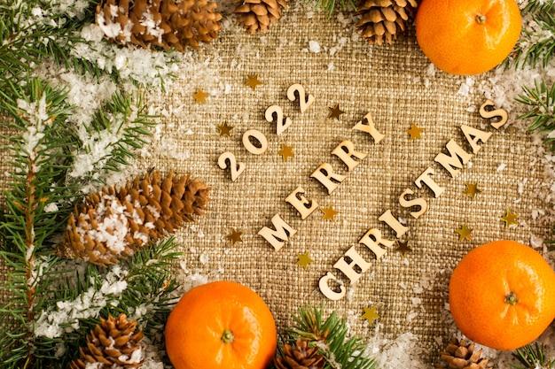 Kerstachtergrond met de nummers van het botte nieuwe jaar, wensen, citrus en besneeuwde takken en kegels. bovenaanzicht.