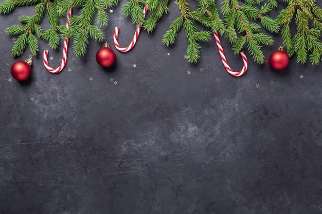 Kerstachtergrond met dennenboom, zuurstokken en rode ballen op donkere stenen achtergrond. bovenaanzicht ruimte kopiëren - afbeelding
