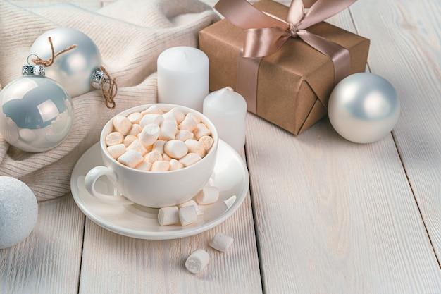 Kerstachtergrond met een kopje koffie, een cadeau en kerstspeelgoed. zijaanzicht, kopieer ruimte.