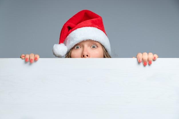 Kerstachtergrond met een persoon met een verbaasd gezicht in een kerstmanhoed