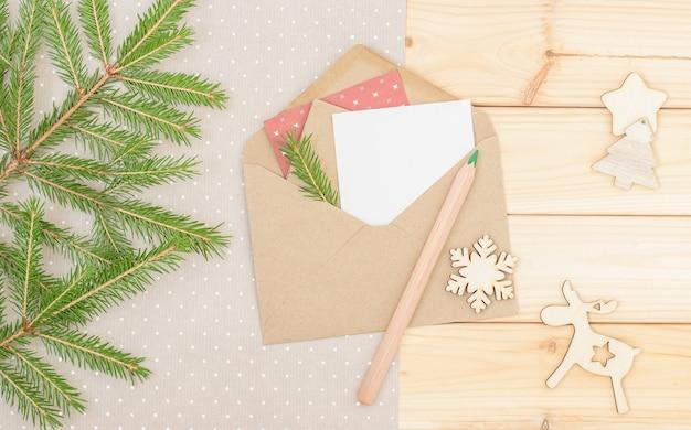 Kerstachtergrond met envelop groene potloodtak van kerstboom ecologisch concept