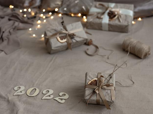 Kerstachtergrond met geschenkdozen verpakt in ambachtelijk papier en houten nummers 2022 op onscherpe achtergrond met slinger.