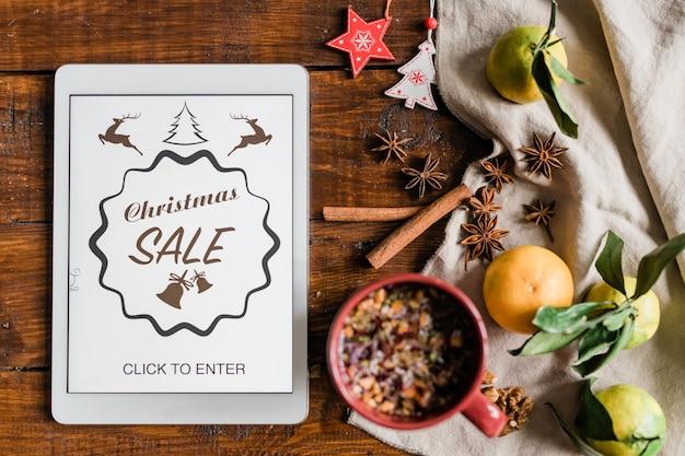 Kerstachtergrond met homepage van online winkel in touchpad, drank, clementines, steranijs, kaneel en decoraties