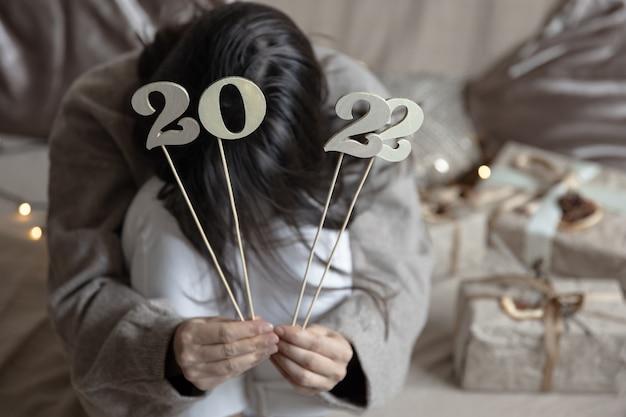 Kerstachtergrond met houten nummers 2022 op stokjes in vrouwelijke handen