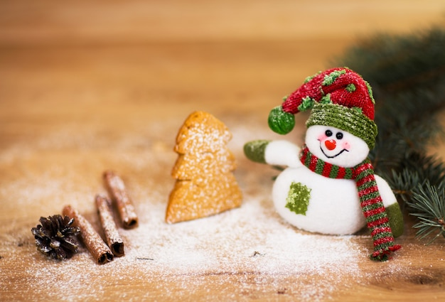 Kerstachtergrond met kerstboom en sneeuwpop op een rustieke houten plank