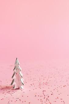 Kerstachtergrond met kleine zilveren kerstboom en kleurrijke glitters op roze