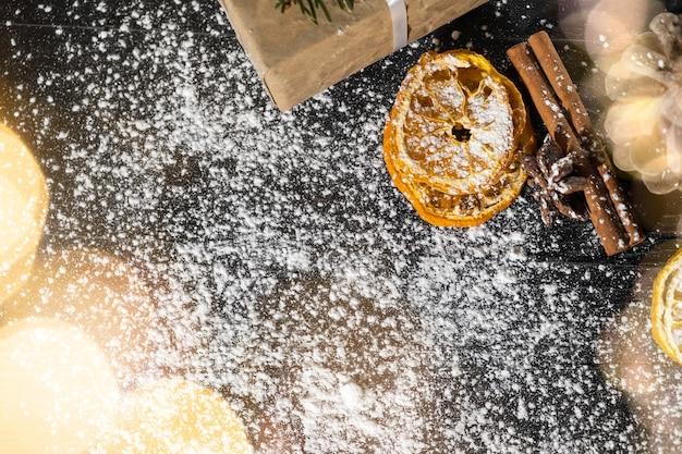 Kerstachtergrond met kopieerruimte, gedroogde snoepjes, kaneelstokjes en zoet suikerpoeder op donkere houten achtergrond. kerst cadeaukaart. nieuwjaar wenskaart.