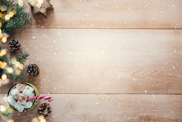 Kerstachtergrond met marshmallow hete chocolote houten sneeuwvlokken en kerstboomtakken