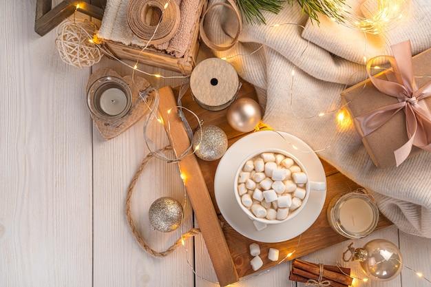 Kerstachtergrond met marshmallow-koffie en kerstversiering in het licht van een brandende slinger. bovenaanzicht, kopieer ruimte.