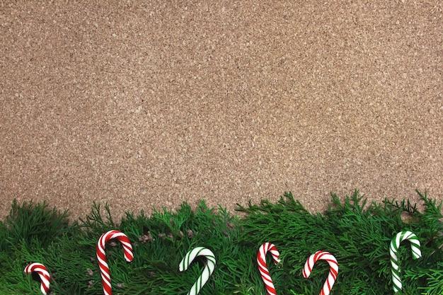 Kerstachtergrond met naaldboomtakken en zuurstokken op een kurkbord