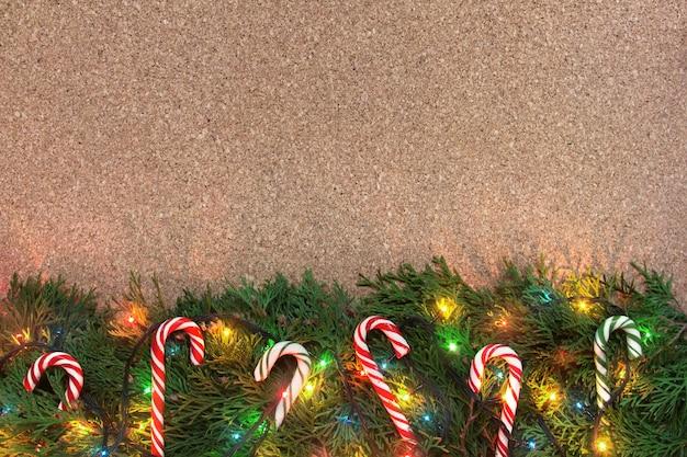 Kerstachtergrond met naaldboomtakken, kleurrijke lichten en snoeprietjes op een kurkbord
