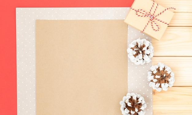 Kerstachtergrond met papieren geschenkdoos en beschilderde kegels