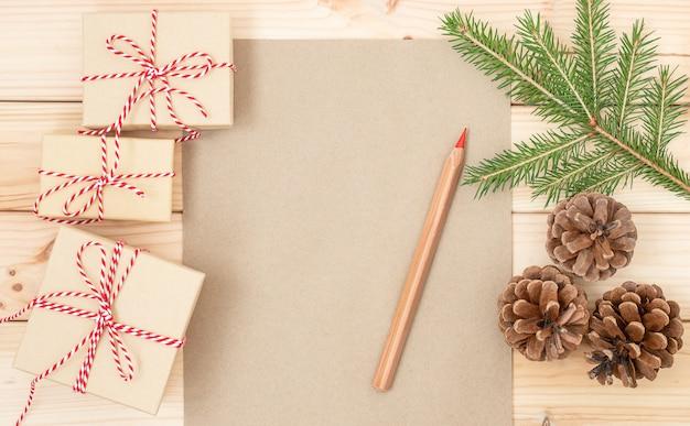 Kerstachtergrond met vel papier rood potlood geschenkdozen tak van sparren en kegels
