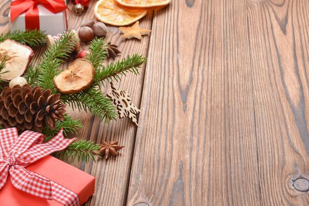 Kerstachtergrond van dennentakken, speelgoed en eco-decoraties op een houten tafel. natuurlijk ontwerp van de nieuwjaarsvakantie. wenskaart voor kerstmis en nieuwjaar.