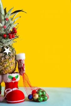 Kerstananas in santa-laarzen, wintervuisthandschoenen en een zak met chocoladekleurige snoepjes