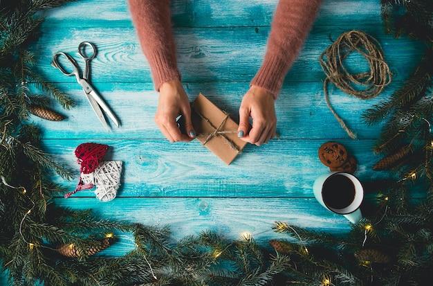Kerstartikelen op een blauwe houten tafel. de handen die van de vrouw kerstmisgift verpakken.