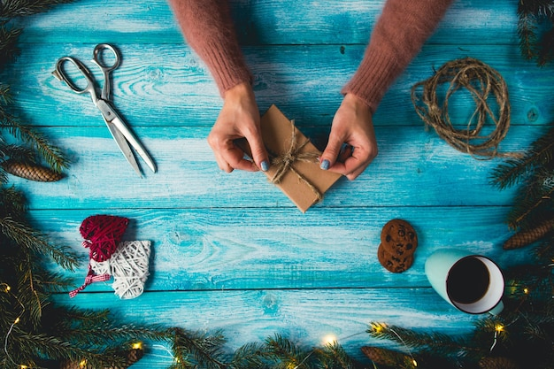 Kerstartikelen op een blauwe wodden tafel. de handen die van de vrouw kerstmisgift verpakken.