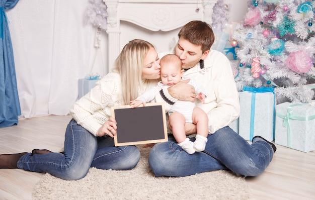 Kerstavond. gelukkige ouders en vier maanden oude zoon.