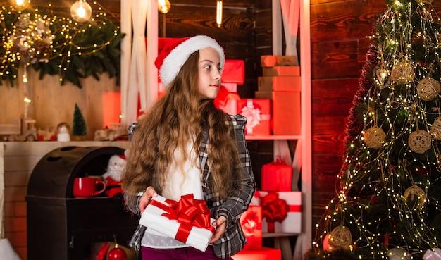 Kerstavond. mode meisje klaar voor kerstviering. kleine fashionista. modieus klein kind. vrolijk kerstfeest. verrassing. de levensstijl die u verdient. wintercadeau. kerstman hoed accessoire.