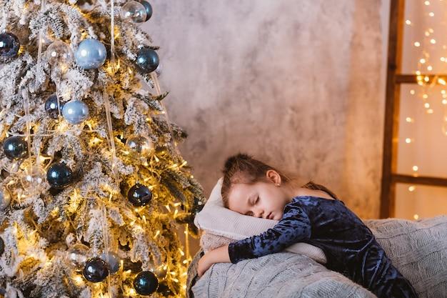 Kerstavond. moe meisje in slaap gevallen op de bank tijdens het wachten op santa met geschenken op versierde fir tree thuis.