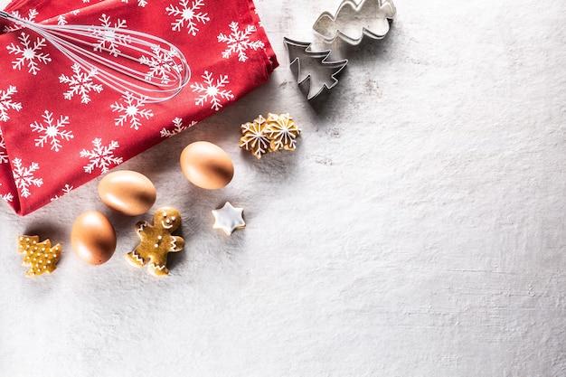 Kerstbakken, peperkoekkoekjes, honing, kaneel en koekjesmessen - kopieer ruimte.