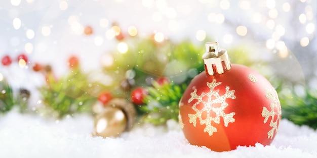 Kerstbal en dennentakken met decoraties.