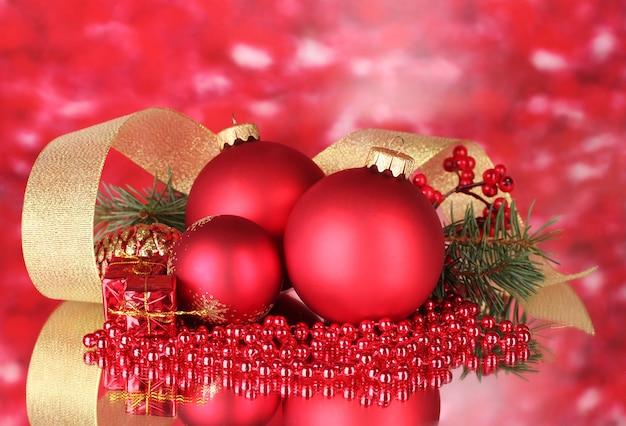 Kerstbal en groene boom op rood