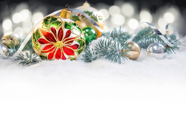Kerstbal met poinsettia, takken van de kerstboom op sneeuw