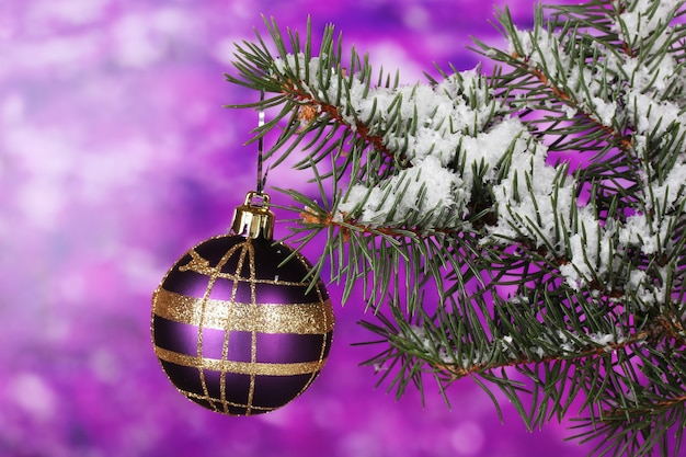 Kerstbal op de boom op paars