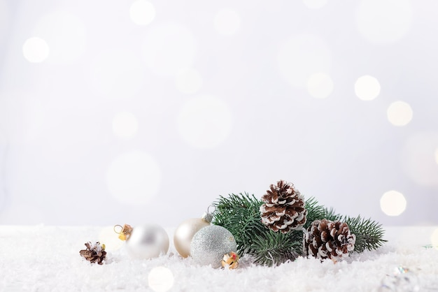 Kerstbal op een fir tak met dennenappel en glitter achtergrond