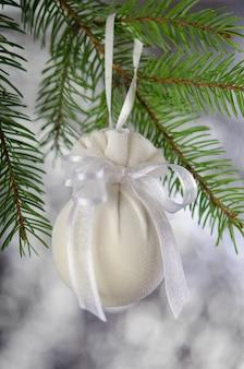 Kerstbal verpakt in medisch masker met wit lint nieuwe jaardecoratie