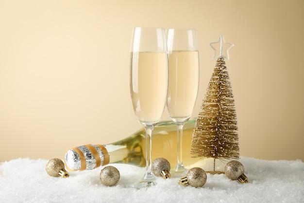 Kerstballen, champagneglazen en fles tegen beige ruimte, ruimte voor tekst