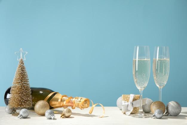 Kerstballen, champagneglazen en fles tegen blauwe ruimte, ruimte voor tekst