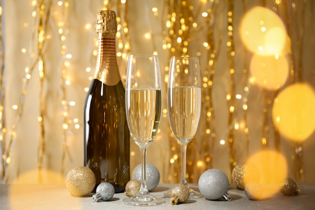 Kerstballen, champagneglazen en fles tegen versierde ruimte. bokeh-effect
