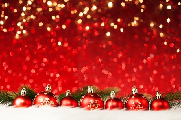 Kerstballen en boom op rood glitter oppervlak