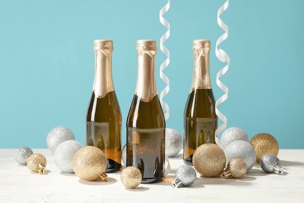 Kerstballen en champagne mini flessen tegen blauwe ruimte, ruimte voor tekst