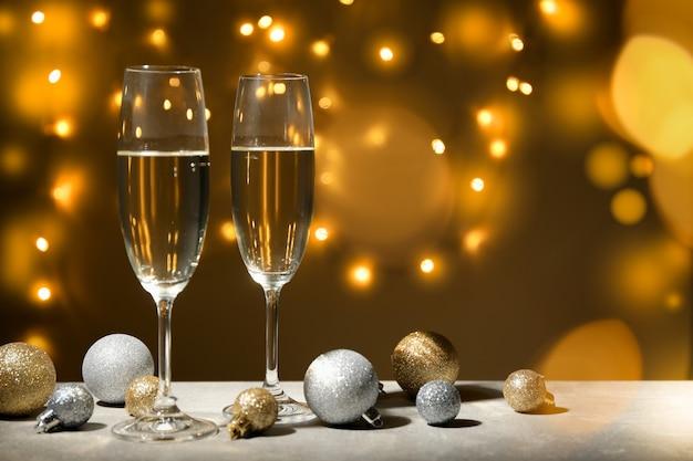 Kerstballen en champagneglazen op ingerichte ruimte. bokeh-effect