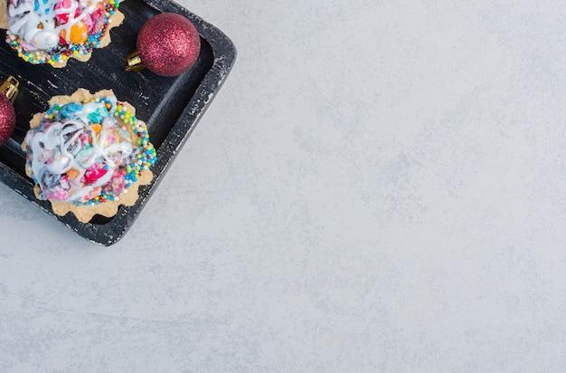 Kerstballen en cupcakes met snoepjes in een zwarte bak op marmeren oppervlak