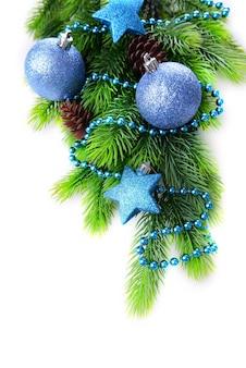 Kerstballen en decoratieve sterren op dennenboom, geïsoleerd op wit